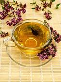 Herbal tea with oregano on bamboo — Stock Photo