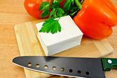 Feta cheese on a board with a knife and vegetables — Stock Photo