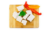 Feta cheese pieces on the board with pepper — Stock Photo
