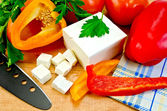 Feta cheese on the board with vegetables and herbs — Stock Photo