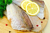Fillet of codfish on a round board — Stock Photo