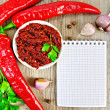 Adjika with fresh chili peppers and a notepad — Stock Photo