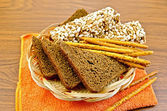 Rye bread and crispbreads in a wicker plate on napkin — Stock Photo