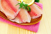 Fillets tilapia in a pottery on a napkin — Stock Photo