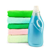 Fabric softener the bottle and a stack of towels — Stock Photo
