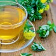 Herbal tea with Rhodiola rosea in the cup on the board — Stock Photo