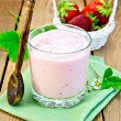 Milkshake with strawberries and spoon on the board — Stock Photo