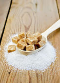 Sugar brown and granulated sugar in a spoon on the board — Stock Photo