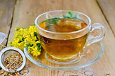Herbal tea from tutsan in strainer with cup — Stock Photo