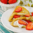 Pancakes with strawberries and basket with berries on a napkin — Stock Photo #32249373