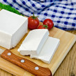 Feta cheese with tomato on the board and napkin — Stock Photo