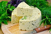 Cheese round homemade with herbs and knife on board — Stock Photo