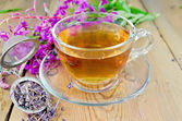 Herbal tea from fireweed in a glass cup with strainer — Stock Photo