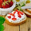 Bread with curd cream and strawberries with a basket — Stock Photo
