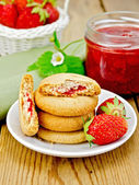 Biscuits with strawberries and a basket on the board — Stock Photo