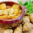 Jerusalem artichokes roasted in a clay pot on a board — Stock Photo