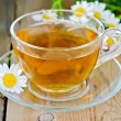 Herbal chamomile tea in a glass cup on a board — Lizenzfreies Foto