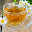 Herbal chamomile tea in a glass cup on a board — Stockfoto