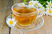 Herbal chamomile tea in a glass cup on a board — Stock Photo