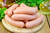 Sausages on a board with parsley — Stock Photo