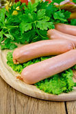 Sausages on a board with parsley and oil — Stock Photo