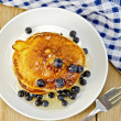 Постер, плакат: Flapjacks with blueberries and a fork on a board