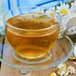 Herbal chamomile tea dry in a strainer with a glass cup — Photo