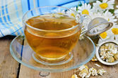 Herbal chamomile tea dry in a strainer with a glass cup — Stock Photo