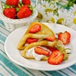Pancakes with strawberries on a napkin — Stock Photo