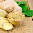 Ginger powder in a bowl with the root and leaves — Stock Photo #35041461