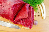 Meat beef on a board with garlic — Stock Photo