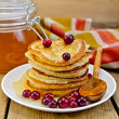 Flapjacks with cranberry and a jar of honey on the board — Stock Photo