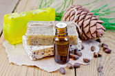 Oil and soap different with cedar nuts and cone on a board — Stock Photo