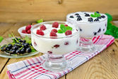 Yogurt thick with black currant and raspberry on the board — Stock Photo