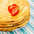 Pancakes on a plate with strawberries on a napkin — Stock Photo