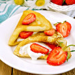 Stock Photo: Pancakes with strawberries and cream on the board