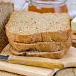 Rye homemade bread stacked with honey and knife — Stock Photo