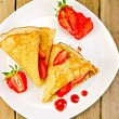 Pancakes with strawberries and jam on plate and board — Stock Photo