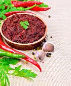 Adjika with hot pepper and garlic on burlap — Stock Photo