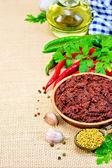 Adjika with hot pepper and a napkin on burlap — Stock Photo