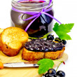 Bread with jam from blackcurrant on a board — Stock Photo