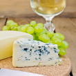 Stock Photo: Cheese different with grapes and wine on board