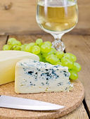 Cheese different with grapes and wine on the board — Stock Photo