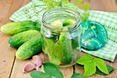 Cucumbers in jar with leaves and napkin on the board — Stock Photo