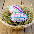 Easter eggs with ribbons and sequins in a basket — Stock Photo