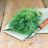 Dill with a knife on board — Stock Photo