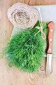 Dill with a knife and twine on the board — Stock Photo