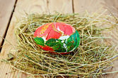 Easter egg with a red flower in the hay — Stock Photo