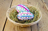Easter eggs with ribbons and sequins in a basket — Stockfoto