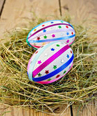 Easter eggs with ribbons and sequins in the hay — Photo